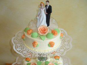Hochzeitstorte aus Buttercreme und Fruchttorte dreistöckig und oben mit Brautpaar - Nahaufnahme