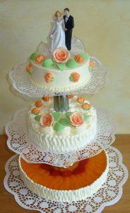 Hochzeitstorte aus Buttercreme und Fruchttorte dreistöckig und oben mit Brautpaar