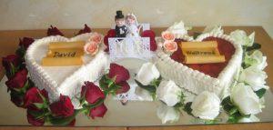 Hochzeitstorte mit Fruchtherz und Buttercremeherz mit Brautpaar und roten & weißen Rosenblüten