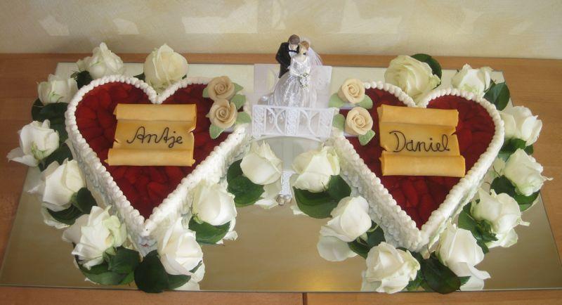 Hochzeitstorten mit Fruchtherzen mit Brautpaar und weißen Rosenblüten