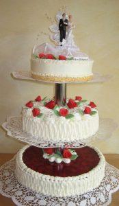 Hochzeitstorte aus Buttercreme und Erdbeer-Fruchttorte dreistöckig und oben mit Brautpaar