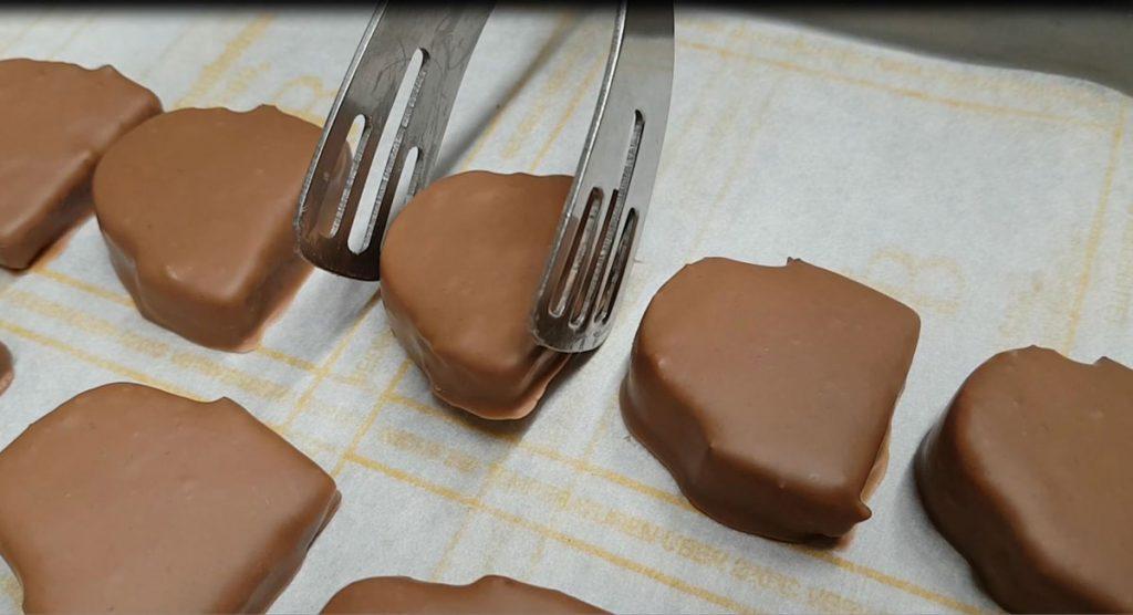 Herstellung von Baumkuchenspitzen die fertig mit Schokolade überzogen sind